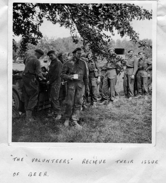"""Volunteers receive their issue of beer""  near Le Mesnil, August 1944"