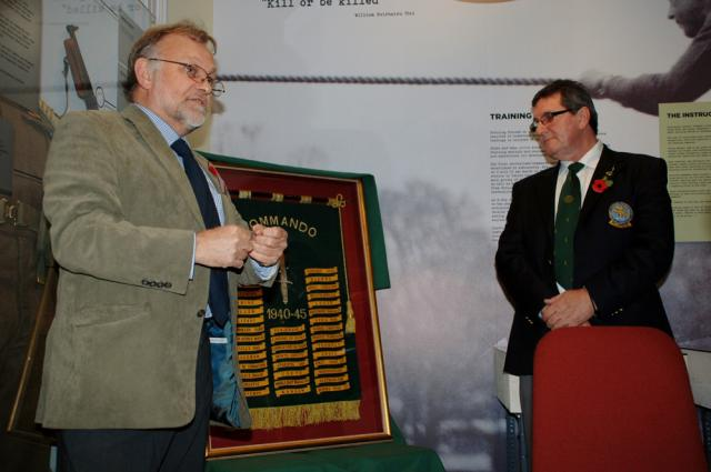 Ron Lane presenting his framed Commando Honours Battle Flag to the West Highland Museum