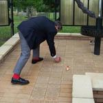 Ron 'Red Socks' Lain places a poppy on Bob Bartholemew's paver