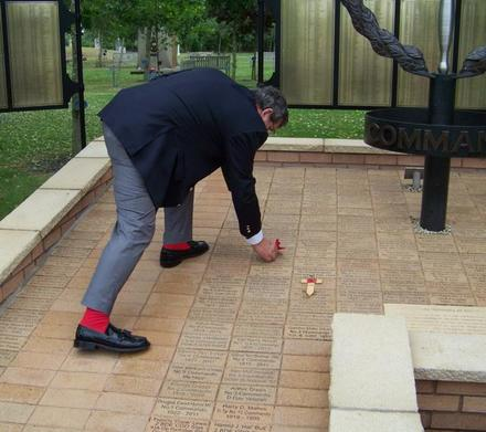 Ron 'Red Socks' Lain places a poppy on Bob Bartholemew's paver