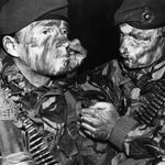 A Royal Marine of 3 Commando Brigade helps another to apply camouflage face paint in preparation for the San Carlos landings on