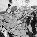 A Belgian commando inspects his rifle with sniper 'scope in a village at the foot of Mt Camino, 6 February 1944.