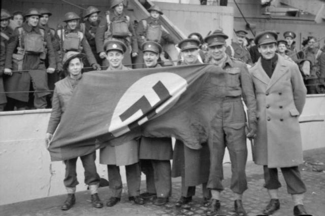British officers with a captured Nazi flag after the raid.